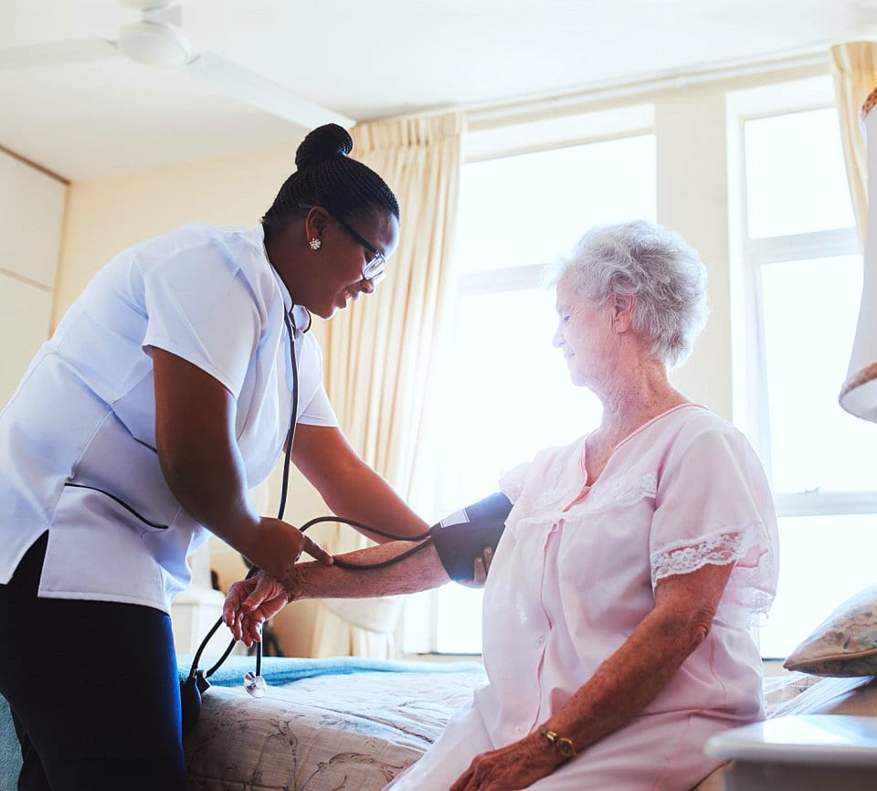 caregiver checking blood pressure of senior woman