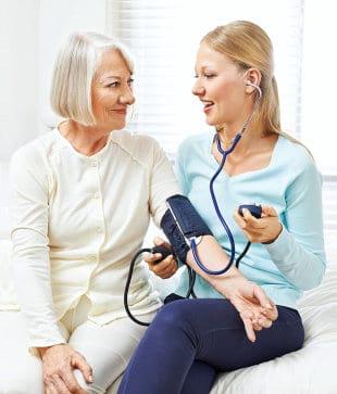 caregiver checking blood pressure of a senior woman
