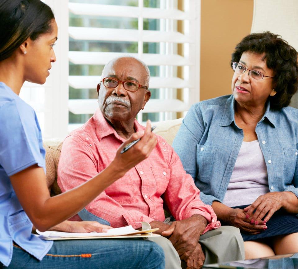 caregiver explaining to senior couple