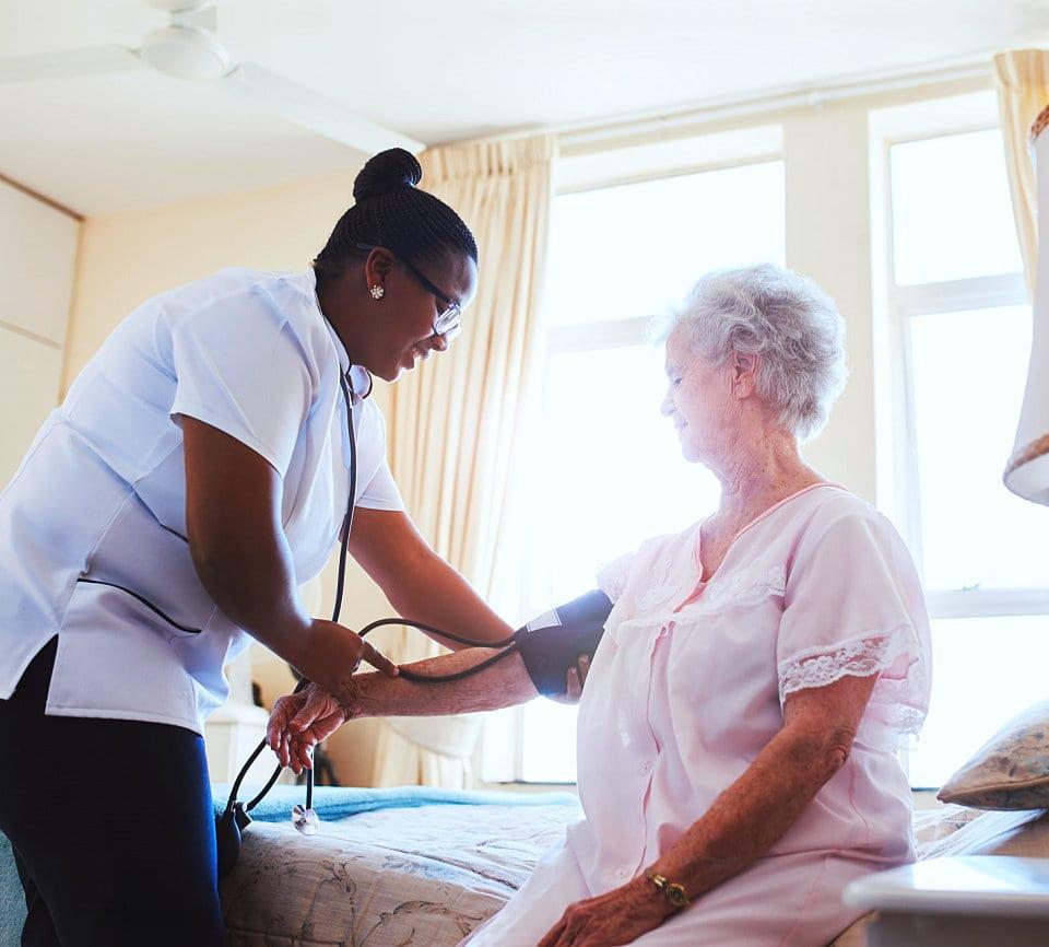 caregiver checking blood pressure of senior woman